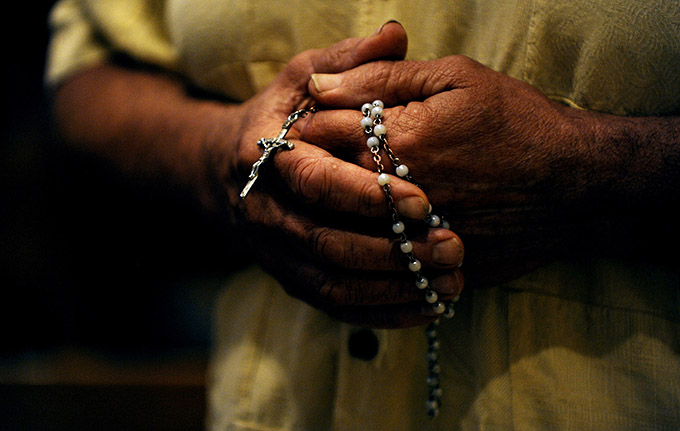 A man prays the rosary during a prayer service. Pope Francis has asked believers world-wide to join him Saturday, Sept. 7 for a day of prayer and fasting for peace in Syria. (CNS file photo/Mike Crupi, Catholic Courier)