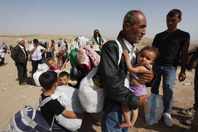 Syrian refugees, fleeing the violence in their country, cross the border into the Kurdish region of northern Iraq Sept. 4. (CNS photo/Haider Ala, Reuters)