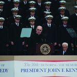 "Dallas Bishop Kevin J. Farrell delivers the invocation Nov. 22 during the ""The 50th: Honoring the Memory of President John F. Kennedy"" ceremony at Dealey Plaza in Dallas. Behind is the U.S. Naval Academy Glee Club. Seated to the bishop's left are historian David McCullough and Dallas Mayor Mike Rawlings. (JENNA TETER/The Texas Catholic)"