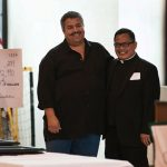 Father Jimwell Goyo of St. James Catholic Church hugs trustee Raul Estrada and receives a grant from The Catholic Foundation Nov. 20 at Holy Family of Nazerath Catholic School.