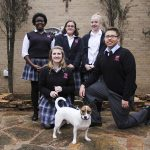 Members of the Bishop Dunne Catholic School Animal Rescue Club, clockwise from back left, Danae Jackson, Maya Hightower, Teresa Slettebeo, J.P. Coronado and Amanda Greene pose with one of their success stories, Henry, a rescued dog.  (Michael Gresham/The Texas Catholic)
