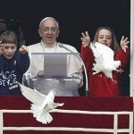 Pope Francis watches as children release doves from window of studio overlooking St. Peter's Square