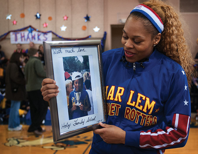 "Joyce ""Sweet J"" Ekworomadu is presented with an old picture of herself as a 5th grader at Holy Family of Nazareth Catholic School in Irving Jan. 27. (JENNA TETER/The Texas Catholic)"