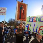 Tim O' Flaherty, of Lewisville, carries a banner of Our Lady of Lebanon as he walks with his family during the Stand4Life: Dallas March for Life, on  Jan. 18 in downtown Dallas. (BEN TORRES/Special Contributor)