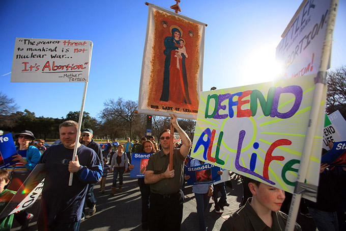 Tim O' Flaherty, of Lewisville, carries a banner of Our Lady of Lebanon as he walks with his family during the Stand4Life: Dallas March for Life, on Saturday, Jan. 18, 2014 in Downtown Dallas. (Ben Torres/Special Contributor)