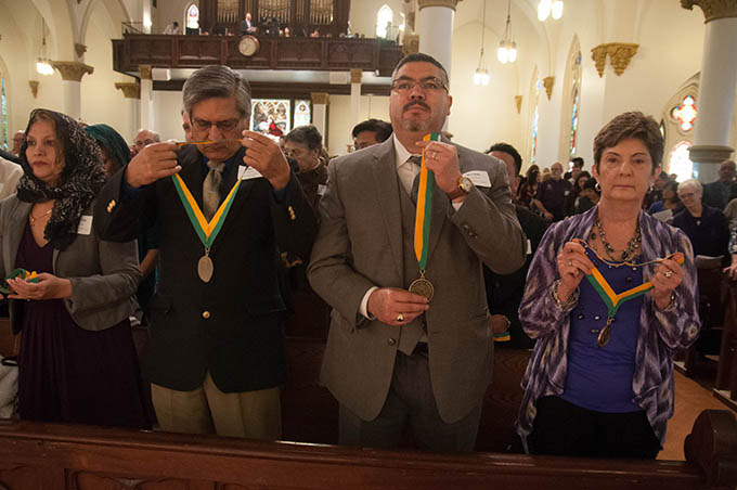 Diocese of Dallas volunteers, from left, Flor Chavira and Jesus Chavira of Divine Mercy of Our Lord Catholic Church in Mesquite, Johnny Ramos and Ann Marie Shubert of Good Shepherd Catholic Parish in Garland hold up their Bishop's Award medals to be blessed by Bishop Kevin J. Farrell during Mass at the Cathedral Shrine of the Virgin of Guadalupe on Feb. 22. (JENNA TETER/The Texas Catholic)