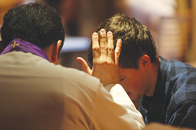 A priest hears a young man's confession during a pro-life gathering in Washington, D.C. (Catholic News Service)