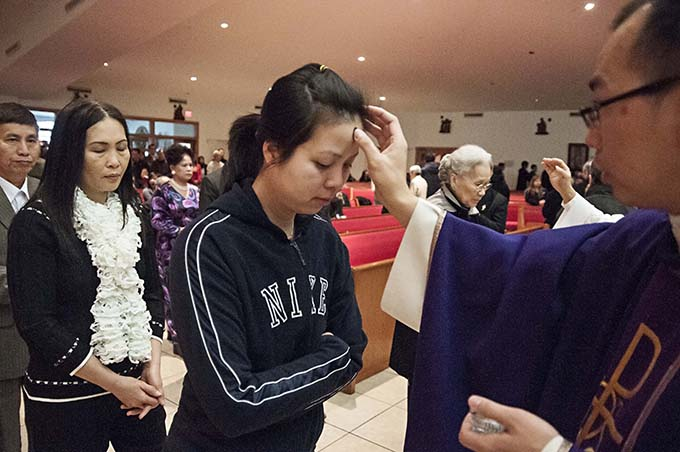 Ming Trang receives ashes from Father Thomas Ha on Ash Wednesday Feb. 13, 2013 at Mother of Perpetual Help Vietnamese Catholic Church in Garland. (JENNA TETER/ The Texas Catholic)