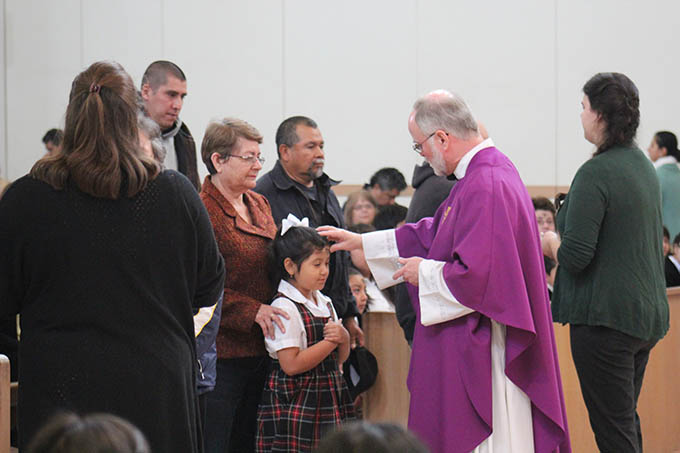 Father Robert Williams, pastor of St. Francis of Assisi Catholic Church in West Oak Cliff, distributes ashes to a student on Ash Wednesday.