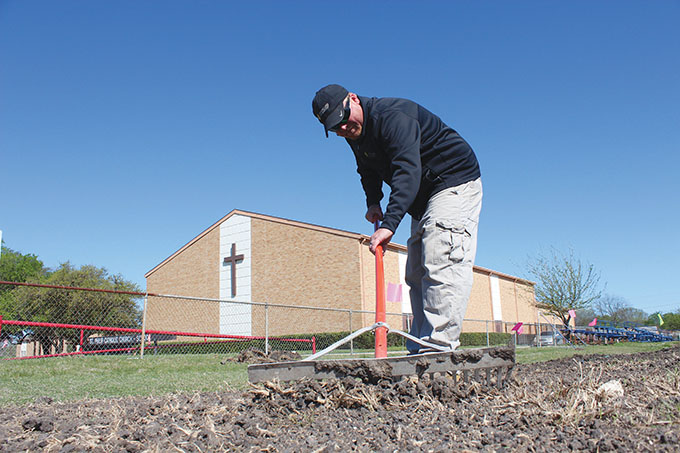 Tom O'Connor prepares soil at the football field at St. Philip the Apostle Catholic School for grading. O'Connor is a project superintendent for Landscapes Unlimited, a partner with Ewing Irrigation Systems, Inc., which will transform the field and other parts of the campus on April 15. (DAVID SEDEÑO/ The Texas Catholic)