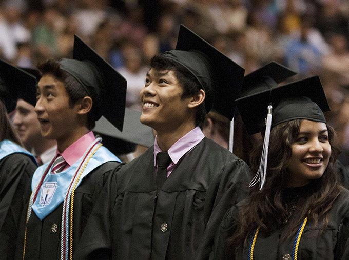 Derek Le, center, smiles as he watches his fellow classmates, on a jumbotron, take their seats at the beginning of the Bishop Lynch High School commencement ceremony May 18 at the Curtis Culwell Center in Garland. (JENNA TETER/The Texas Catholic)