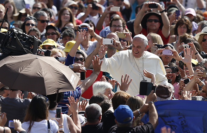 Pope Francis greets the crowd as he arrives to lead his general audience in St. Peter's Square at the Vatican June 18. (CNS photo/Paul Haring)