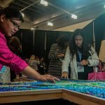 Attendees help create a collaborative, glass rock cross as part of the liturgical art display at the University of Dallas Ministry Conference Oct. 23 at the Irving Convention Center. (JENNA TETER/The Texas Catholic)