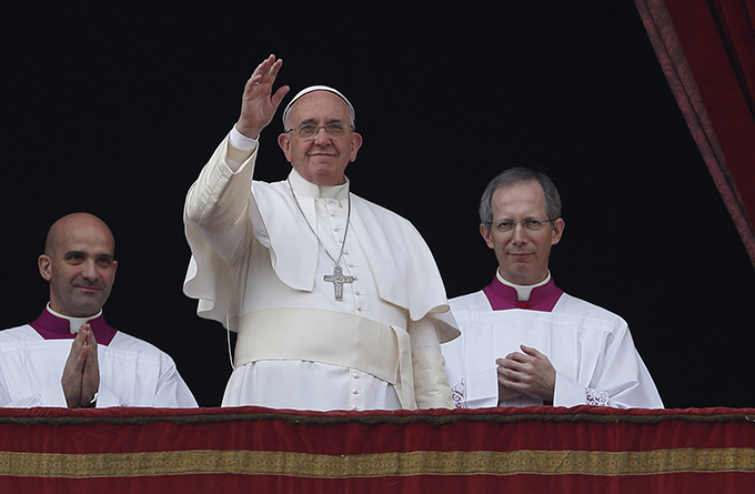 "Pope Francis waves after delivering his Christmas blessing ""urbi et orbi"" (to the city and the world) from the central balcony of St. Peter's Basilica at the Vatican Dec. 25. (CNS photo/Paul Haring)"