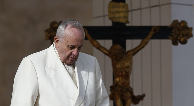 Pope Francis passes a crucifix during his general audience in St. Peter's Square at the Vatican Dec. 3. (CNS photo/Paul Haring)
