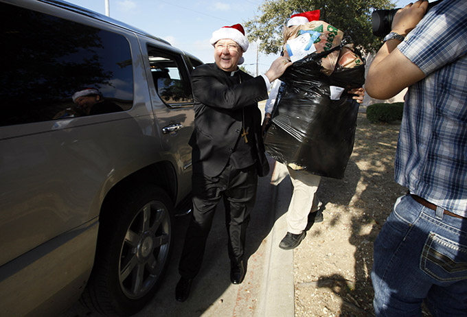 Bishop Kevin J. Farrell prepares to place a bag of toys in a vehicle during the Catholic Charities of Dallas Christmas Distribution event on Dec. 13 at Santa Clara Regional Community Center. The gifts were donated by parishes, schools and individuals.