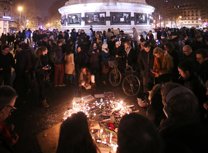 "People light candles as they gather in Paris to commemorate the victims and condemn the killings at offices of Charlie Hebdo, a satirical newspaper, Jan. 7. Pope Francis condemned the killings of at least 12 people at the offices of the publication Jan. 7 and denounced all ""physical and moral"" obstacles to the peaceful coexistence of nations, religions and cultures. (CNS photo/Fredrik Von Erichsen, EPA)"