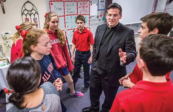 Father Alfonse Nazzaro interacts with eighth-grade students at All Saints Catholic School on Dec. 18. (RON HEFLIN/Special Contributor)