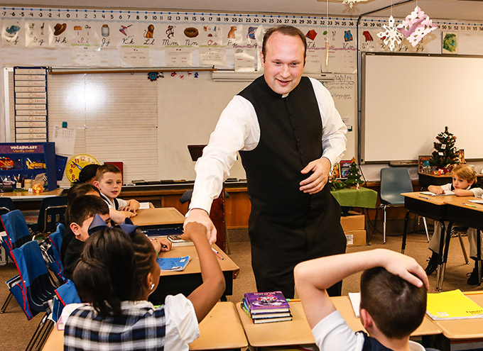 Father Jason Cargo, pastor of Immaculate Conception Catholic Church in Corsicana, gives a fist bump to Ellysa Crouch while talking to third-grade students in Thelma Lockwood's classroom at James L. Collins Catholic School. (DON JOHNSON/Special Contributor)