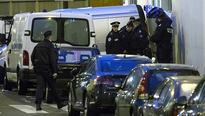 """French police evacuate the bodies of the victims after a mass shooting at the Paris offices of Charlie Hebdo, a satirical newspaper, Jan. 7. Pope Francis condemned the killings of at least 12 people at the offices of the satirical newspaper Jan. 7 and denounced all """"physical and moral"""" obstacles to the peaceful coexistence of nations, religions and cultures. (CNS photo/Etienne Laurent, EPA)"""