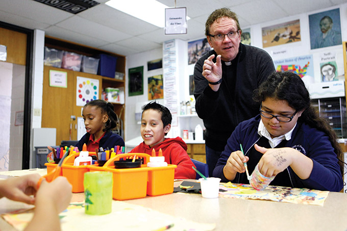 Father Michael Dugan visits with sixth-grade students during an art class at St. Elizabeth of Hungary Catholic School on Dec. 11 in Oak Cliff. (BEN TORRES/Special Contributor)