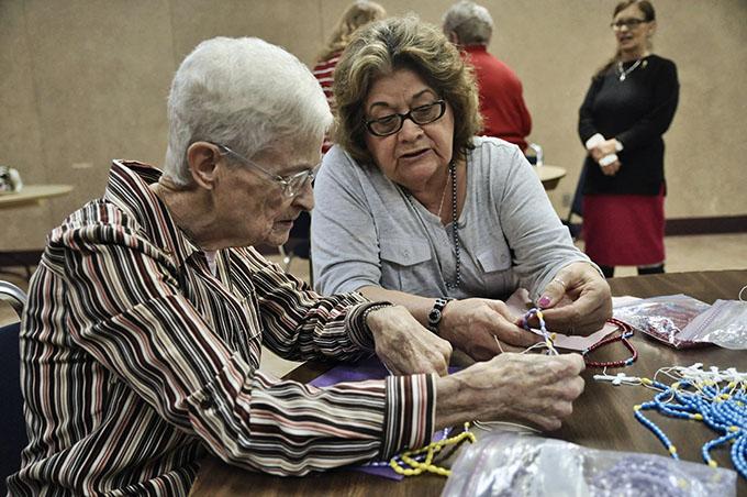 Parishioner Micaela Olivarez, right, shows Philomena Mattingly, how to put together a holiday rosary at Holy Spirit Catholic Church in Duncanville on Dec. 2. (JENNA TETER/The Texas Catholic)