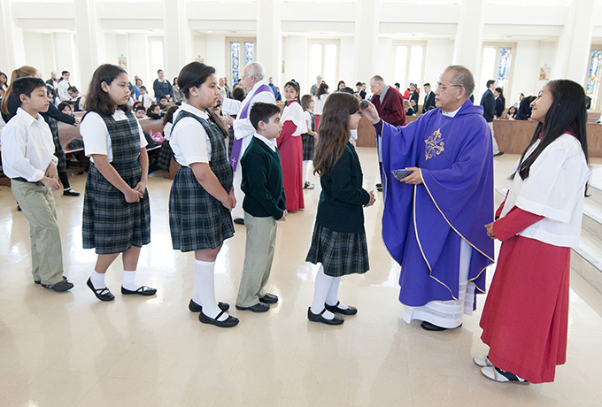 Father Edmundo Paredes distributes ashes to fourth-grader Arlette Luis during an all-school Mass on Ash Wednesday at St. Cecilia Catholic Church Feb. 18. (JENNA TETER/The Texas Catholic)