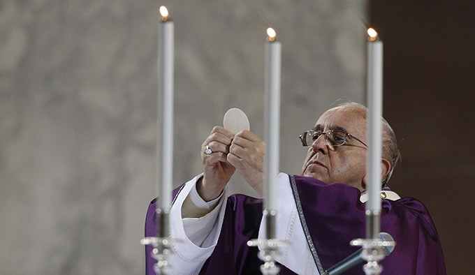 Pope Francis elevates the Eucharist during Ash Wednesday Mass at the Basilica of Santa Sabina in Rome Feb. 18. (CNS photo/Paul Haring)