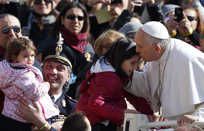 Pope Francis kisses a child as he arrives to lead his general audience in St. Peter's Square at the Vatican March 18. (CNS photo/Paul Haring)