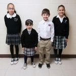 St. Augustine's Emma Antunez, left, and St. Philip the Apostle's Lily Parra, at right, wear the current respective uniforms, while, bottom row Ximena Carranza, left, and Pietro Miele model what the new St. Philip & St. Augustine Catholic Academy uniforms could look like. (JENNA TETER/The Texas Catholic)
