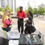 Cheryl Flores, left, talks to interested passersby during an outreach effort by the St. Paul Street Evangelization group in the Dallas Arts District April 11. (DON JOHNSON/Special Contributor)