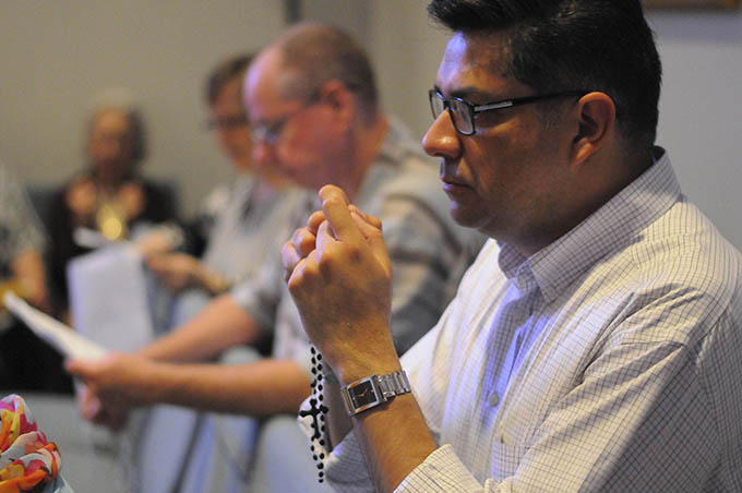 Martin Castaneda follows along with a prayer while kneeling in front of a picture of a man to be executed in the coming months during a special prayer session April 26 at St. Gabriel the Archangel Catholic Church in McKinney. (JENNA TETER/The Texas Catholic)