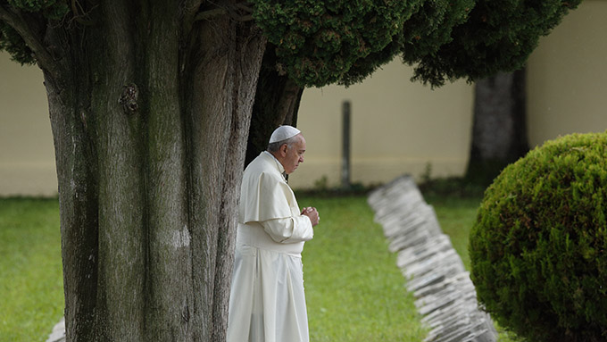 "Pope Francis is shown praying at an Austro-Hungarian cemetery for fall soldiers of World War I in Fogliano di Redipuglia, northern Italy, Sept. 13, 2014. The pope in his encyclical ""Laudato Si', on Care for Our Common Home,"" released June 18, said all creation is singing God's praise but people are silencing it. (CNS photo/Paul Haring)"