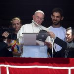Pope Francis is flanked by two Polish youths as he uses a tablet to officially open online registration for World Youth Day 2016 in Poland. (CNS photo/Ettore Ferrari, EPA)