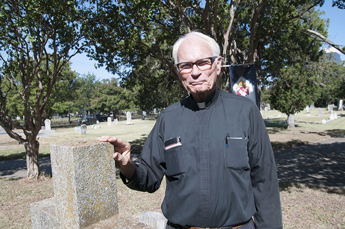 Father Timothy Gollob, pastor of Holy Cross Catholic Church in Oak Cliff, stands among the headstones in the historic Old Calvary Cemetery, located on N. Hall Street in Dallas. (JENNA TETER/The Texas Catholic)