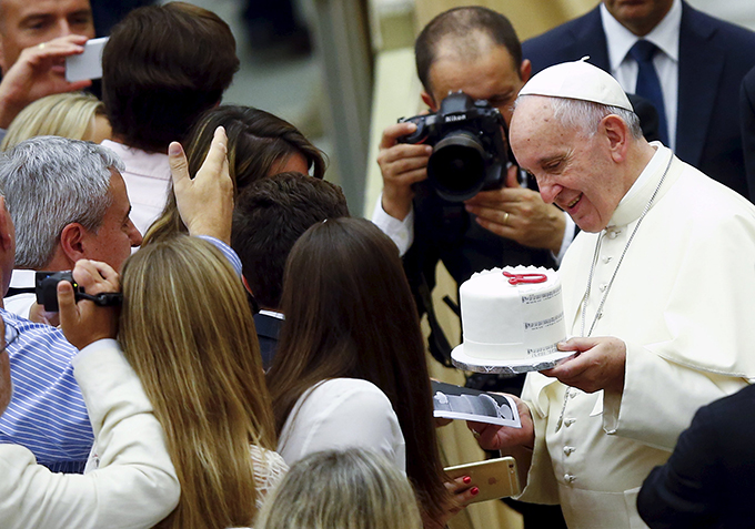 Pope Francis holds a cake he received from a newly married couple during his weekly audience in Paul VI hall at the Vatican Aug. 12. (CNS photo/Remo Casilli, Reuters)
