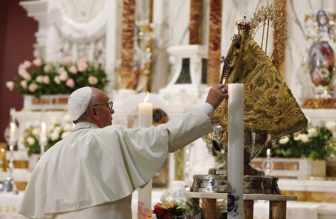 Pope Francis lights a candle at the statue of Our Lady of Charity, patroness of Cuba, in the Minor Basilica of the Shrine of Our Lady of Charity in El Cobre, Cuba, Sept. 21. (CNS photo/Paul Haring)