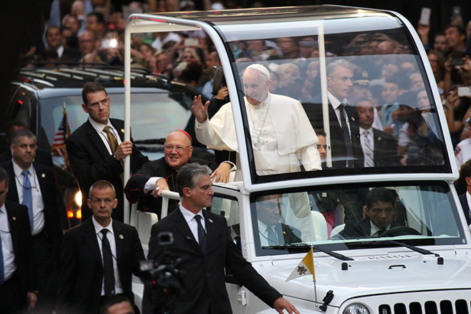 Pope Francis waves to the crowds as he approaches St. Patrick's Cathedral in New York City Sept. 24. Seated next to him is Cardinal Timothy M. Dolan of New York. (CNS photo/Gregory A. Shemitz)