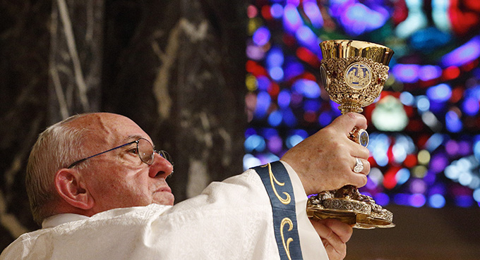Pope Francis raises the chalice of the Eucharist as he celebrates Mass with representatives from the Archdiocese of Philadelphia at the Cathedral Basilica of SS. Peter and Paul in Philadelphia Sept. 26. (CNS photo/Paul Haring)