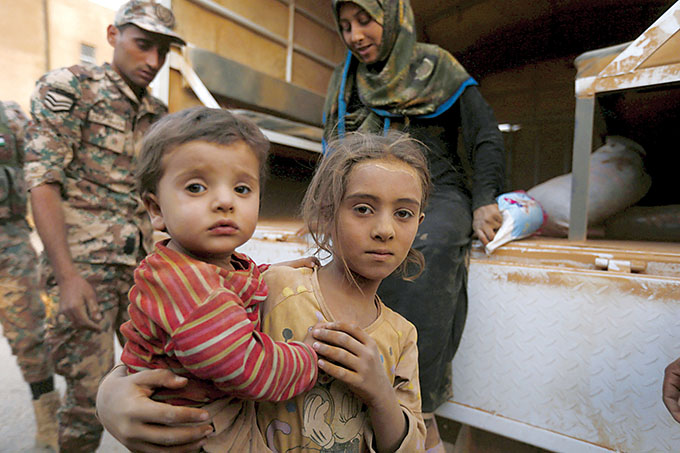 Syrian refugee children covered with dust arrive Sept. 10 at the Jordanian border with Syria and Iraq, near the town of Ruwaished, which is close to Amman, Jordan. (CNS photo/Muhammad Hamed, Reuters)