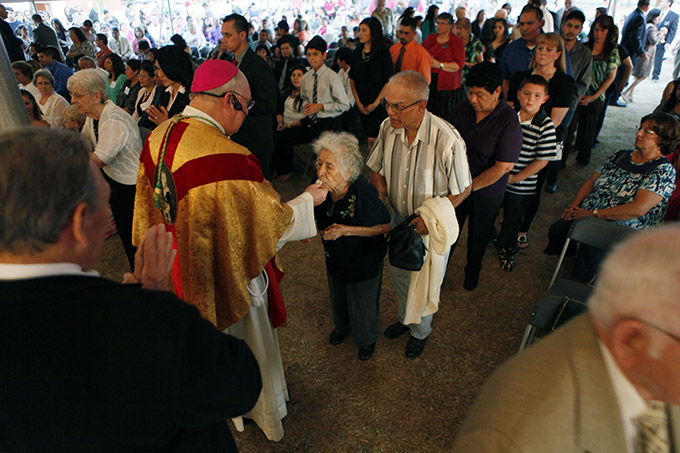Bishop Kevin J. Farrell distributes communion to Nelly González during a special 125th Anniversary Mass for the Diocese of Dallas on Oct. 3 at Immaculate Conception Catholic Church in Corsicana, which has the distinction of being the oldest continuously operating parish in the diocese. (BEN TORRES/Special Contributor)