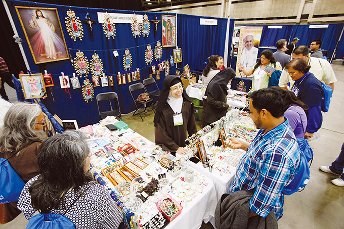 Blanca Maria Peña, of the Hermanas Carmelitas Descalsas, speaks with Antonio Ortiz, right, as he browses for a crucifix during the University of Dallas Ministry Conference 2015, on Oct. 24 at the Kay Bailey Hutchison Convention Center in Dallas. (Ben Torres/Special Contributor)