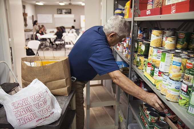 Tom Germino, president of the St. Vincent de Paul Conference at St. Francis of Assisi Catholic Church, collects items listed on an order form to put into a food bag for a client in the food pantry in Lancaster. (JENNA TETER/The Texas Catholic)