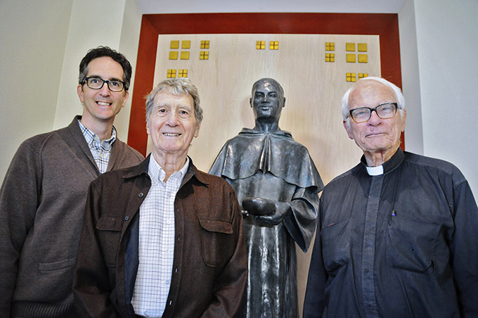 Father Tim Gollob with artists David and Lyle Novinski in front of their statue of St. Martin de Porres inside Holy Cross Catholic Church. (JENNA TETER/The Texas Catholic)