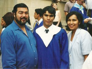 Gabriel Moreno, center, poses with his parents, Luis and Rachel Moreno, following his Bishop Dunne graduation ceremony in 2003.
