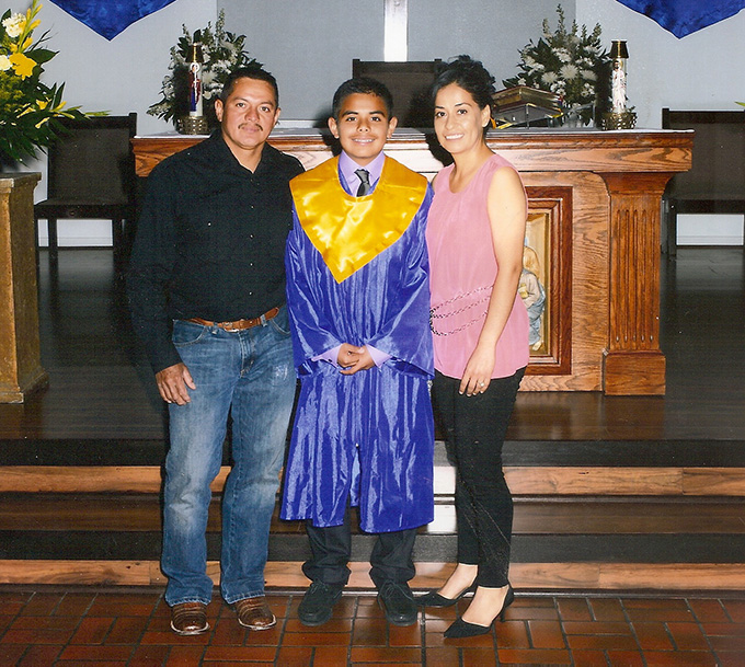 Kenndrick Mendieta with his parents following his eighth-grade graduation from St. Augustine Catholic School.