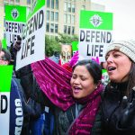 Ellanie Berba, left, and Jasmin Penny, both parishioners at St. Michael the Archangel Catholic Church in McKinney, sing at a pro-life rally outside the Earle Cabell Federal Building. (RON HEFLIN/Special Contributor)