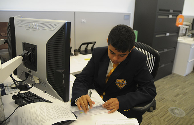 Kenndrick Mendieta checks paperwork details at his desk during his work study at HFF, a commercial real estate financing company in downtown Dallas' Victory Park. JENNA TETER/The Texas Catholic)