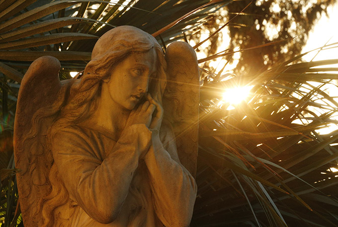 Sun backlights a decorative angel on a tombstone in Verano cemetery in Rome. (CNS photo/Paul Haring)