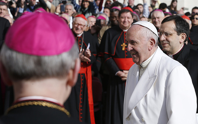 Pope Francis walks past cardinals and bishops as he arrives to lead his general audience in St. Peter's Square at the Vatican Feb. 24. (CNS photo/Paul Haring)